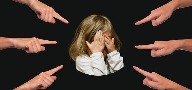 指を指される少女