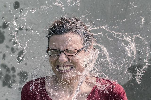 水をかけられて驚く女性