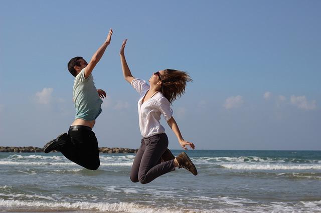 ジャンプしながらハイタッチする男女