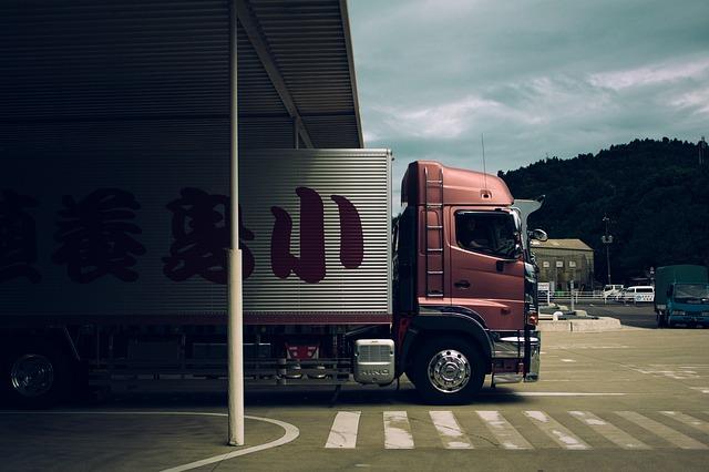 倉庫から出発するトラック
