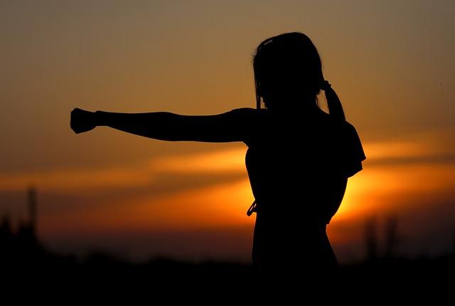 拳を突きだす女性のシルエット